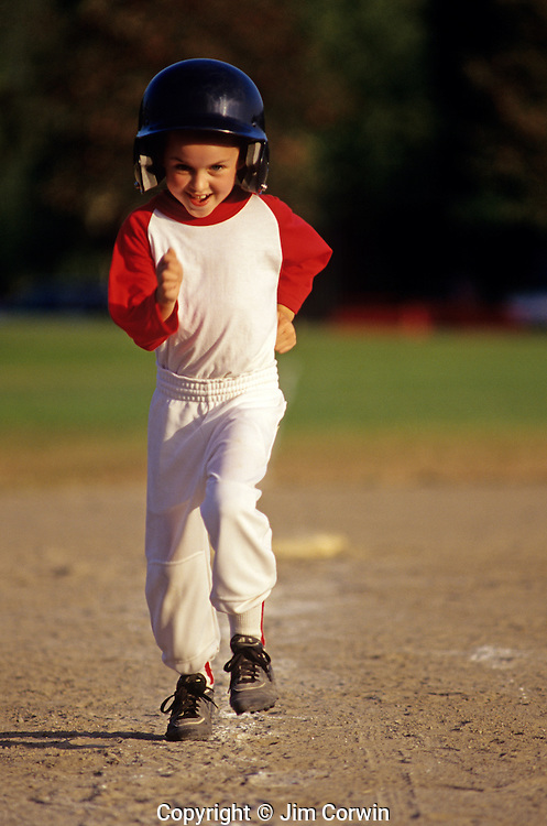 Young girl Little League Baseball player rounding third base heading for home plate