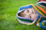 A beautiful young woman lies on the green grass as she's wrapped up in a colorful knit blanket.
