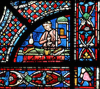 A chemist preparing a remedy with a pestle and mortar, donor window of the apothecaries, from the Life of St Nicholas stained glass window, 13th century, in the North aisle of the nave of Chartres cathedral, Eure-et-Loir, France. St Nicholas, 270-343 AD, was born in Patara in Lycia (now Turkey) and was bishop of Myra. Chartres cathedral was built 1194-1250 and is a fine example of Gothic architecture. Most of its windows date from 1205-40 although a few earlier 12th century examples are also intact. It was declared a UNESCO World Heritage Site in 1979. Picture by Manuel Cohen