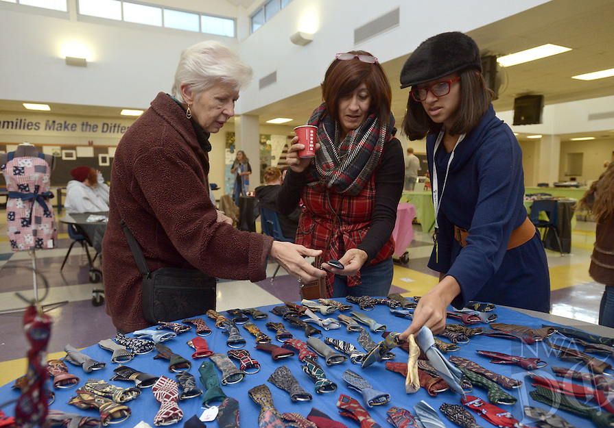 NWA Democrat-Gazette/BEN GOFF @NWABENGOFF<br /> Misa Fontana (from right), a freshman at Rogers New Technology High School and her mother Margarita Fontana of Rogers and grandmother Edie Fontana from The Villages, Fla. look at Modern Edge dog neck ties made by Destani (CQ) Cogdill (not pictured), a Crossroads senior, on Monday Dec. 19, 2016 during the Project 479 Christmas Bazaar at the Crossroads alternative education campus in Rogers. The school holds the bazarr, as well as one in the spring, to allow high school students to showcase their creativity by making and selling crafts.