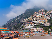 Hillside buildings in Positano at Amalfi Coast, Italy, World Heritage Site. Beach chairs, recliners and sunshades.