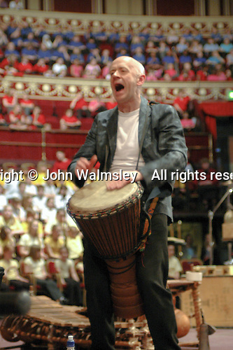 Buckinghamshire Schools Concert rehearsal at the Royal Albert Hall, London, with percussion group, Three Strange Angels.  Chris Brannick playing the djembe drum which dates back to 12th century West Africa.