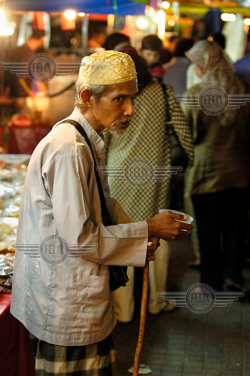 Old Muslim beggar at the downtown Saturday night Pasar Malam (night market) close to Little India and Jalan Tunku Abdul Rahman.