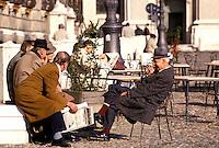 Mantova, Piazza Sordello, uomini seduti ai tavolini di un bar.<br /> Mantua, Piazza Sordello, men sitting at an outdoor cafe.