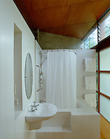 The circular shape of the shower curtain rail is echoed by the circular mirror which hangs above the wash basin