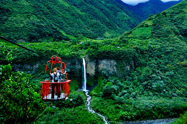 Tourists ride a cable car over the canyon of the Rio Pastaza, and enjoy  spectacular views of the the Manto de la Novia waterfall and the tropical landscapes of the Andes Mountains.