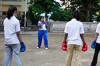 Razia Shabnam (in blue) conducts a boxing training session with a group of girls from an NGO in a park in Basduni, Tolly Gunge, Calcutta, West Bengal, India. Razia Shabnam, 28, was one of the first women boxers in Kolkata. She was also the first woman in her community to go to college. She is now a coach and one of only three international female boxing referees in India.  Photo by Suzanne Lee for Panos London