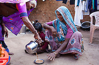An upper caste woman (left) serves tea to a Dalit midwife in a saucer meant for people of the Dalit caste, in a house where Video Volunteer videojournalist Niru J. Rathod, 24, is doing an interview on topics of caste discrimination in a remote village in Surendranagar, Gujarat, India on 14 December 2012. The last time Niru had come to their home, she was discriminated against and served tea in a saucer meant for lower castes. Now, after seeing the effects of her video activism, the family no longer discriminates against her. Niru, the 8th child in a family of 11 girls born to a Dalit construction worker, has been using videography for social change since 2006. She shoots and produces her own short documentaries and is a committed video activist, having conducted hundreds of village video screenings where she also speaks to thousands of men, shattering their ideas about what a woman and a Dalit can do while bringing massive changes to the communities she documents. Photo by Suzanne Lee / Marie Claire France