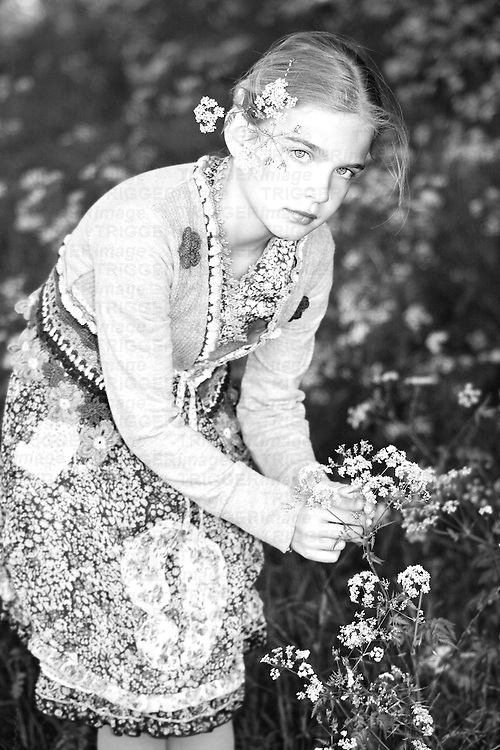 Young girl wearing summer dress picking flowers in garden