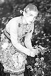 Young girl wearing summer dress picking flowers in garden