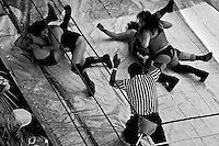 """Female Lucha libre wrestlers pin down their rivals during a fight at a local arena in Mexico City, Mexico, 30 April 2011. Lucha libre, literally """"free fight"""" in Spanish, is a unique Mexican sporting event and cultural phenomenon. Based on aerial acrobatics, rapid holds and the use of mysterious masks, Lucha libre features the wrestlers as fictional characters (Good vs. Evil). Women wrestlers, known as luchadoras, often wear bright shiny leotards, black pantyhose or other provocative costumes. Given the popularity of Lucha libre in Mexico, many wrestlers have reached the cult status, showing up in movies or TV shows. However, almost all female fighters are amateur part-time wrestlers or housewives. Passing through the dirty remote areas in the peripheries, listening to the obscene screams from the mainly male audience, these no-name luchadoras fight straight on the street and charge about 10 US dollars for a show. Still, most of the young luchadoras train hard and wrestle virtually anywhere dreaming to escape from the poverty and to become a star worshipped by the modern Mexican society."""