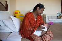 Idan, the surrogate who just gave birth to Barbara's baby, comes to breastfeed the baby in Barbara's hotel room near the Akanksha Clinic in Anand, Gujarat, India on 11th December 2012. Barbara, from Canada, had come to receive him at his birth from Idan, her surrogate, and is waiting for her husband to come and join her in Anand, while she continues to hire Idan to breastfeed her son. Idan's husband sends pumped breast milk to Barbara's hotel in the evenings when Idan cannot come personally. Photo by Suzanne Lee / Marie-Claire France