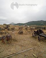 Americana Series: Roadside Views<br /> <br /> Farm machinery graveyard with view of the Black Hills of South Dakota.