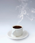 Cup of steaming aromatic black hot coffee on a plate isoltaed silhouette on gray gradient background. Break for lunch, relaxation, breakfast conceptual still life.