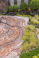 Crazy paving in patio with ornamental grasses creates feeling of movement in the garden