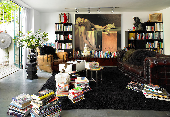 A study room with a leather Chesterfield sofa, armchair and a collection of books on shelves and in stacks on the floor. A print of La Mort de Marat by Jacques-Louis David hangs on the wall.