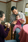 "Berkeley CA Adoptive parents (Cuban father) teaching daughter to make hand sign for ""more"" (asking for food)  MR"