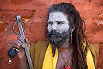 A hindu sadhu (holy man) posing against a red brick wall, at the holy temples of Pashupatinath, Kathmandu.<br />