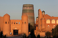 General view of Matniyaz Divan-begi madrasah (right) 1871, Kalta Minor (centre) 1855, and Ota Darvoza (Father Gate) (left), Khiva, Uzbekistan, pictured on July 5, 2010, at sunset. Khiva's old city, Ichan Kala, is surrounded by 2.2 kilometres of crenellated and bastioned city walls. Some sections may be 5th century, but the strongest sections were built 1686-88 by Arang Khan. The main gate today is the restored western Ota Darvoza (Father Gate). Commissioned by Muhammad Niyaz the rectangular, Madrasah has a traditional main facade, its high portal, decorated with majolica, having a central pentahedral niche and corner guldastas which are geometrically patterned in blue, white and green, with green brick domes. The Kalta Minor or Short Minaret was commissioned by Mohammed Amin Khan in 1852 to stand 70 m. high, but was abandoned when he died in 1855, and remains only 26 m. high. Khiva, ancient and remote, is the most intact Silk Road city. Ichan Kala, its old town, was the first site in Uzbekistan to become a World Heritage Site(1991). Picture by Manuel Cohen.