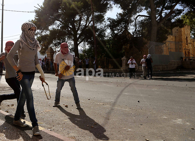 A female Palestinian protester uses a sling to throw stones at Israeli troops during clashes in the West Bank city of Bethlehem October 14, 2015. Seven Israelis and 30 Palestinians, including children and assailants, have been killed in two weeks of bloodshed in Israel, Jerusalem and the occupied West Bank. The violence has been partly triggered by Palestinians' anger over what they see as increased Jewish encroachment on Jerusalem's Al-Aqsa mosque compound. Photo by Muhesen Amren