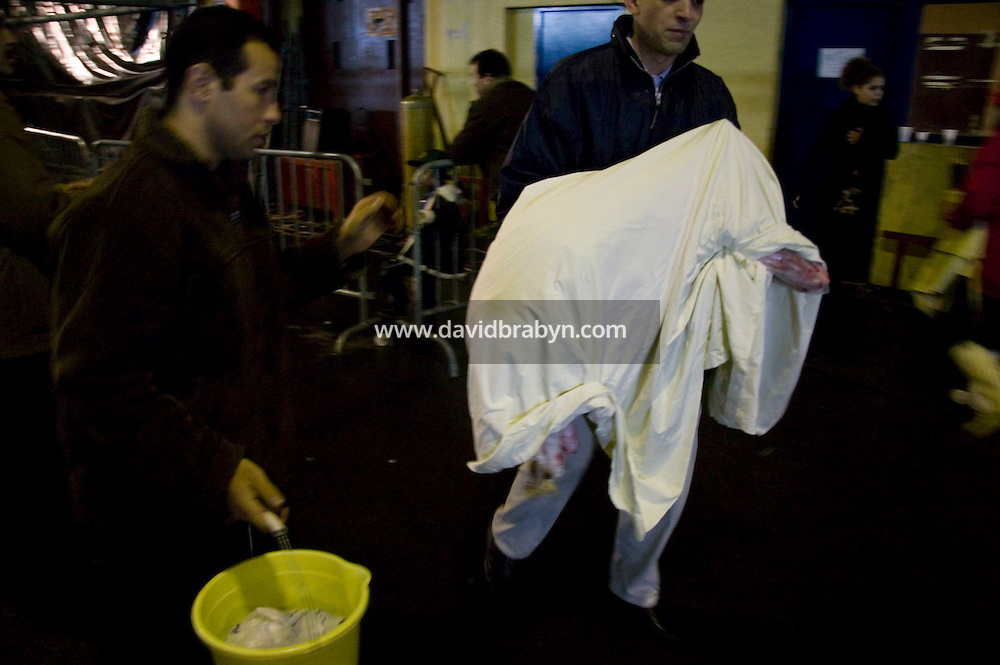 A man carries a carcass of a freshly slaughtered sheep wrapped in a sheet in a temporary slaughterhouse set up in an hanger in Pantin, outside Paris, France, 1 February 2004, during the ritual sheep slaughter held for the Muslim celebration of Aid-el-Kebir. Photo Credit: David Brabyn.