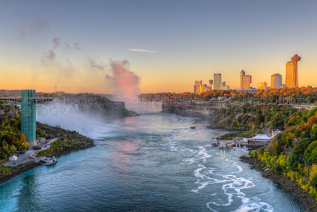 A view of the Niagara River including the American Falls, Horseshoe Falls, and skyline of Niagara Falls, Ontario in golden light just after sunrise.