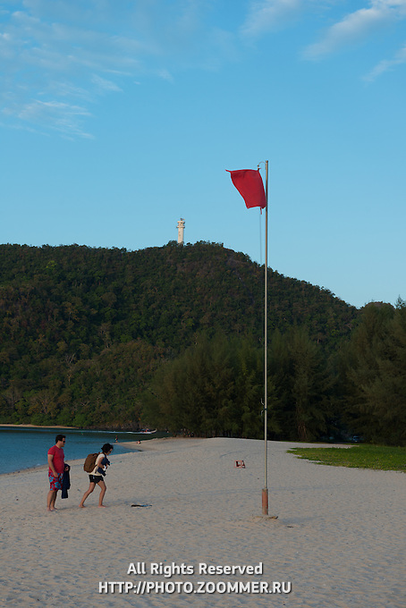 People leaving Tanjung Rhu beach with red flag, Langkawi, Malaysia