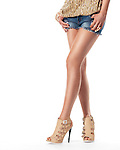 Closeup of sexy young woman legs wearing shorts and high heel shoes isolated on white background
