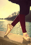 A ballerina in toe shoes balances on a ledge in front of water.