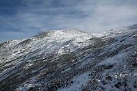 Mount Washington in November with blue skies and fair weather clouds over head. Mount Washington is the tallest peak in the norteastern United States at 6,288 feet tall, and is home to some of the world's worst weather.