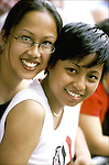 Asian-American Lesbian couple - in crowd, watching  Gay & Lesbian Pride Parade - NYC.