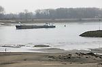 Foto: VidiPhoto<br /> <br /> TOLKAMER - De rivier trekt zich terug. De Waal oogt dinsdag als een relatief smalle stroom ter hoogte van Tolkamer bij Lobith. Nooit eerder was de waterstand in de hele maand januari zo laag als nu. De Rijn en de Waal hebben een extreem laag peil: bij Lobith schommelt de waterstand rond de 7.20 en 7.25 meter boven NAP. Rijkswaterstaat beschouwt een waterstand van 10,30 meter als normaal voor deze tijd. Voordeel is vrije doorgang van de schepen bij de sluizen. Nadeel is dat er minder lading meegenomen kan worden en er dus meer schepen moeten varen voor dezelfde hoeveelheid lading. Het is niet duidelijk of het laagterecord van 2001 gehaald gaat worden: iets minder dan 6,89 meter bij Lobith. Het blijft voorlopig nog droog in het stroomgebied van de Rijn, maar de temperatuur in Duitsland stijgt snel. Dat betekent dat sneeuw gaat smelten en dus meer water in de Rijn.