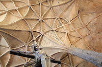 Statue of Christ on the cross, and the rib vaults of the ceiling of the nave above, in the Jeronimos Monastery or Hieronymites Monastery, a monastery of the Order of St Jerome, built in the 16th century in Late Gothic Manueline style, Belem, Lisbon, Portugal. The monastic complex includes the church with portal by Joao de Castilho, cloisters, and Chapel of St Jerome. The monastery is listed as a UNESCO World Heritage Site. Picture by Manuel Cohen