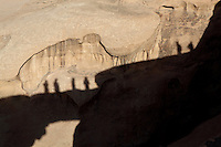Shadows of people standing on Natural sandstone Arch Burdah Rock Bridge, silhouetted against a sandstone mountain, Wadi Rum Protected Area (WRPA), Wadi Rum National Park, also known as The Valley of the Moon, 74,000-hectare, UNESCO World Heritage Site, desert landscape, southern Jordan, Middle East. Picture by Manuel Cohen