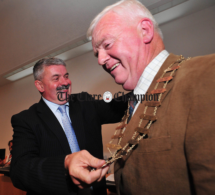 Tony Mulcahy, outgoing Mayor of Clare, passes the mayoral chains to Christy Curtin after his election as Mayor at Aras An Chláir. Photograph by Declan Monaghan