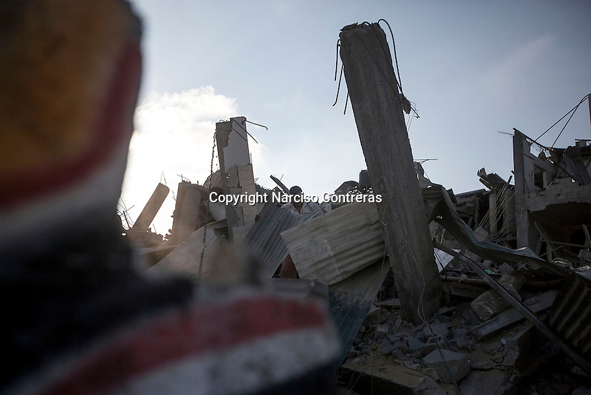 """In this Saturday, Aug. 16, 2014 photo, a Palestinian man looks for his belongings among the rubble of his house destroyed by israeli airstrikes and artillery shelling during the """"Protective Edge"""" military operation in Beit Hanoun neighborhood in Gaza City. After a five days truce was declared on 13th August between Hamas and Israel, civilian population went back to what remains from their houses and goods in Gaza Strip. (Photo/Narciso Contreras)"""