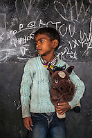 Irfan, 6, poses for a portrait with a soft toy in the Guria Non-Formal Education center in the middle of the Shivdaspur red light district, Varanasi, Uttar Pradesh, India on 20 November 2013. Guria uses the soft toys as a form of therapy for the children of the women in prostitution and also use it as signals of the children's emotional wellbeing.