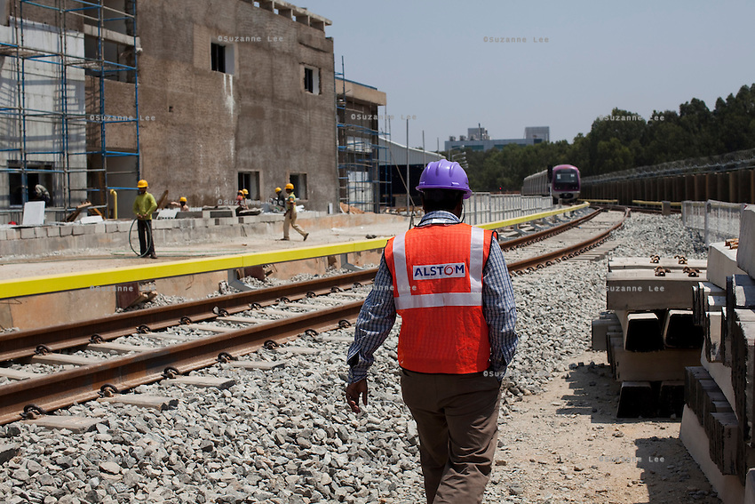 Railway workers and ALSTOM's workers (in purple hardhats) walk by the Third Line Power Supply rails (yellow rails) in the Baiyappanahalli depot station in Bangalore, Karnataka, India on 10th March 2011. .Photo by Suzanne Lee/Abaca Press