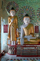Myanmar, Burma.   Umin Thounzeh, Buddhist Shrine on Sagaing Hill, near Mandalay.  The seated Buddha is demonstrating the bhumisparsha mudra (gesture), in which Buddha calls upon the earth to witness his enlightenment, his realization of buddahood.