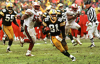 """Desmond Howard returns a punt 71 yards for a touchdown during the NFC Divisional Playoff Game against the 49ers on January 4, 1997. Dubbed the """"Mud Bowl"""", the Packers emerged the victor 35-14."""