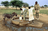 Sudan. West Darfur. Kerenek. A group of children fill water in a plastic jerrycan by using a hand pump on a water well. © 2004 Didier Ruef