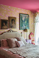This pretty feminine bedroom is furnished with a French bed with a cane headboard