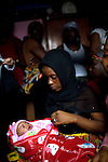 Aisha, a friend of the family holds Mommy's baby...Mommy delivered and died after delivery from postpartum bleeding at the PCMH (Princess Christian Memorial Hospital). Freetown, Sierra leone.
