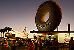 Space Shuttle Endeavour stops in front of Randy's Donuts as it's transported on Manchester Avenue while being moved from Los Angeles International Airport to its retirement home at the California Science Center in Exposition Park in Los Angeles, California, October 12, 2012..
