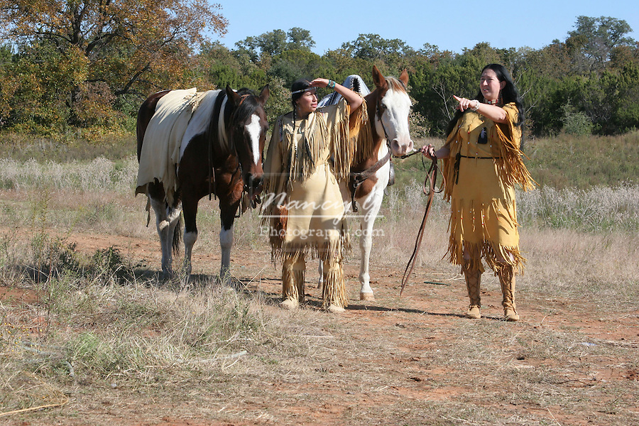 Two Native American Indian women walking their horses on the lookout for danger