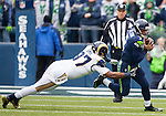 Seattle Seahawks quarterback Russell Wilson (3) is tackled for a six-yards loss by St. Louis Rams Eugene Sims (97) in the fourth quarter at CenturyLink Field in Seattle, Washington on December 29, 2013.  Seahawks clinched the NFC West title and home-field advantage throughout the playoffs with a 27-9 victory over the St. Louis Rams.   Wilson completed 15 of 23 passes for 172 yards and one touchdown in the win. ©2013. Jim Bryant Photo. ALL RIGHTS RESERVED.