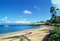 Kapalua Beach, Maui, Hawaii; with people sunbathing on beach, catamaran sailboat at anchor and Molokai island in the distance.