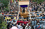 """Participants carry a portable shrine on which is mounted a black phallus made from stone in the grounds of Wakamya Hachimangu shrine during the Kanamara Festival in Kawasaki, Japan on 04 April 2010. The fertility festival, often just called the """"penis festival,"""" has been held since the early 1600s and also aims to promote awareness of AIDS and STDs.."""