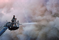 Firemen On Ladder Spraying Water Into Thick Smoke, Manhattan, New York City, New York, USA