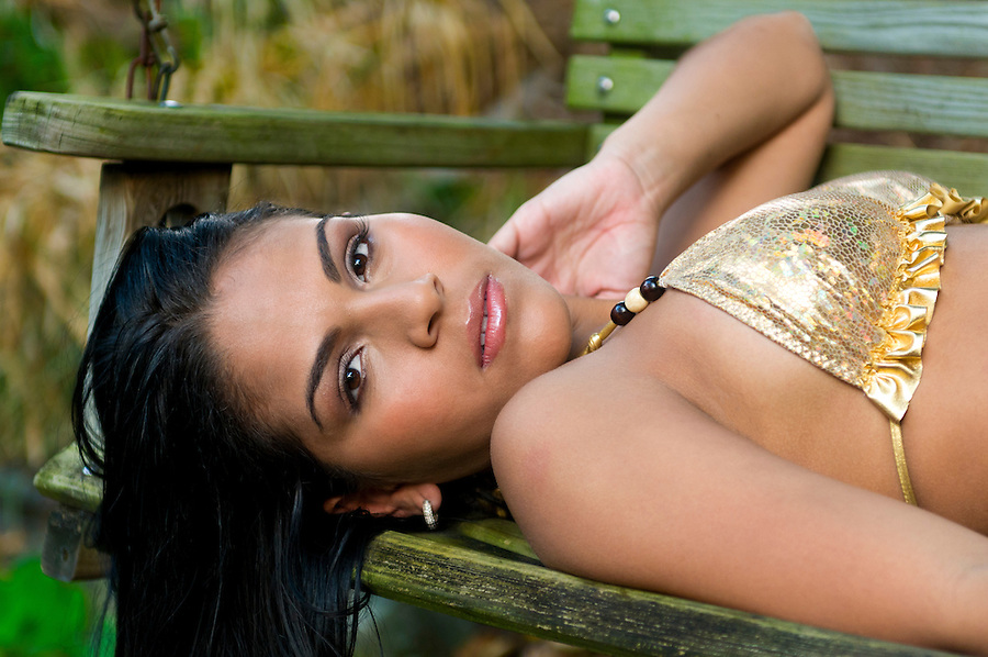 Portrait of hispanic young woman relaxing in a bench in swimwear